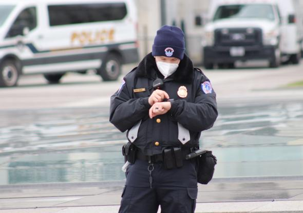 A police officer checks his watch on Jan. 6, 2021 prior to the Capitol breach in Washington, D.C. (Elvert Barnes, https://flic.kr/p/2kqc3v6; CC BY-SA 2.0, https://creativecommons.org/licenses/by-sa/2.0/)