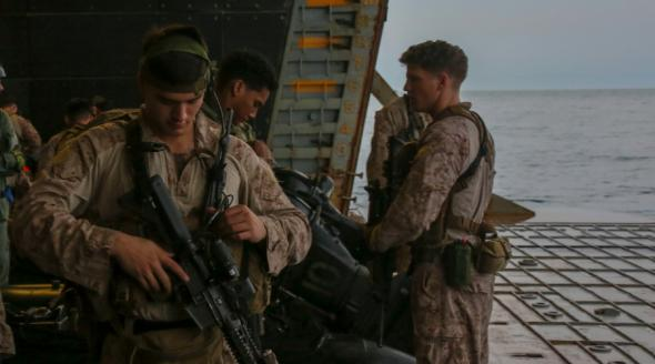 Marines stand aboard the amphibious assault ship USS Bataan, deployed to the 5th Fleet area of operations, on April 15, 2020. Photo credit: U.S. Marine Corps photo by Cpl. Gary Jayne III